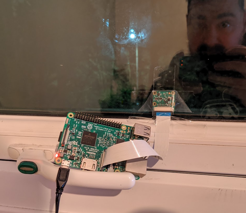 raspberry pi with camera module stuck to a window with Sellotape